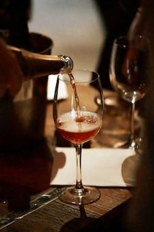 Un chorrito de champán rosado llena la copa sobre la mesa de madera.