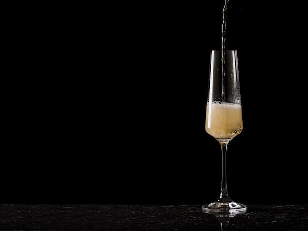 Un chorro de vino espumoso que fluye hacia un vaso alto sobre un fondo negro. una bebida alcohólica popular.