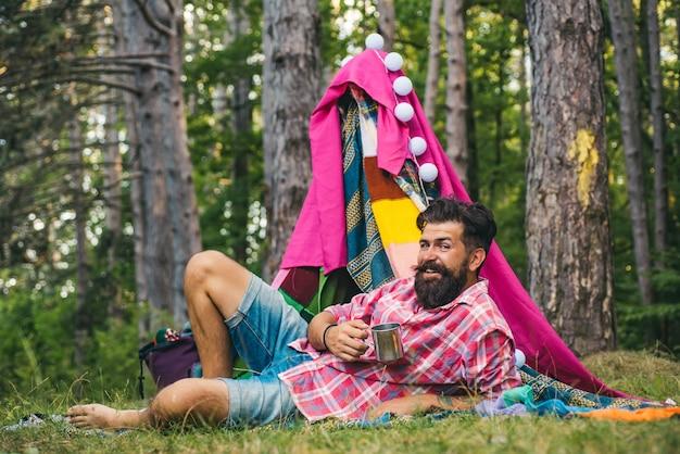 Choza de ramas resto historia de campamento en choza hombre barbudo guapo dentro de tienda de campaña recreación de viaje ...