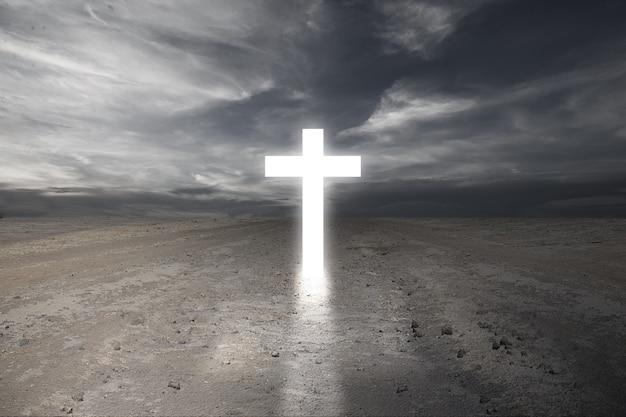 Christian cross en el suelo seco con un espectacular fondo de cielo