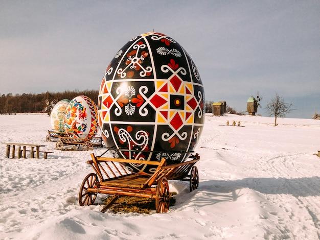 Christmasgiant huevos decorativos con adornos en un trineo en la nieve.