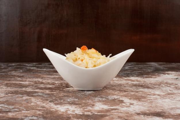 Chucrut casero en un recipiente blanco sobre la mesa de mármol.
