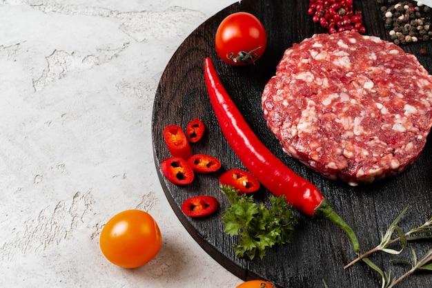 Chuleta casera cruda fresca con especias y tomates en la mesa, cerrar