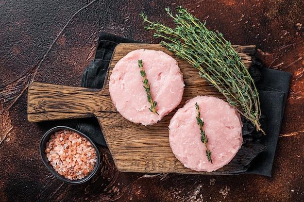 Chuleta de empanada de hamburguesas crudas frescas de carne de pollo y pavo con hierbas. fondo oscuro. vista superior.