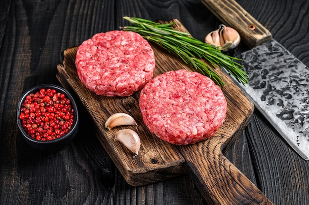 Chuletas de bistec crudo con carne picada de ternera y romero sobre una tabla de cortar de madera con cuchillo de carnicero