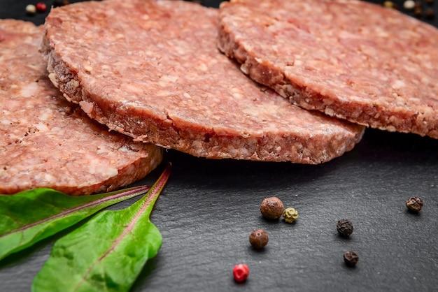 Chuletas de bistec de hamburguesa de carne molida cruda sobre fondo de mármol oscuro.