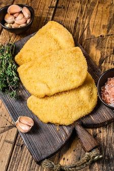 Chuletas de carne cordon bleu con pan rallado sobre una tabla de madera.
