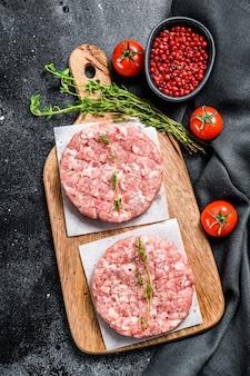 Chuletas de cerdo cruda, carne molida en una tabla de cortar. carne picada orgánica. fondo negro. vista superior