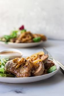 Chuletas de cerdo jugosas fritas con cebolla caramelizada y salsa servidas con ensalada verde y frijoles