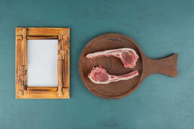 Chuletas de cordero crudo sobre tabla de madera con marco de imagen.