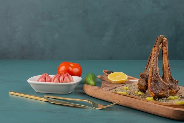 Chuletas de cordero a la plancha sobre tabla de madera con verduras.