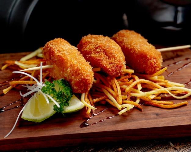 Chuletas de pollo servidas con papas fritas