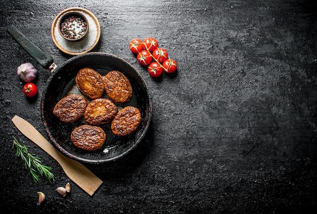 Chuletas en la sartén con espátula de madera y cereza. sobre fondo rústico negro