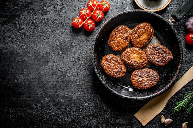 Chuletas en la sartén con una espátula de madera y cereza sobre mesa de madera negra