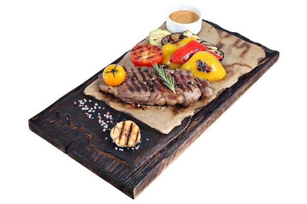 Chuletón a la plancha sobre tablero de madera oscura con pergamino quemado, verduras y salsa aislado sobre fondo blanco.