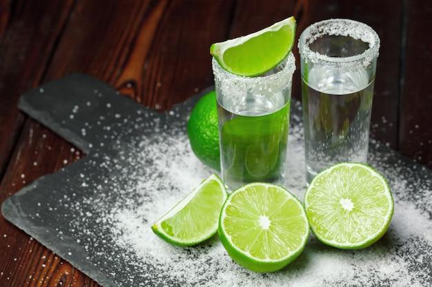 Chupitos de tequila plateado con rodajas de limón y sal sobre tabla de madera