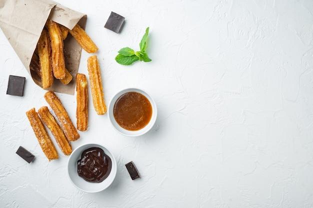 Churros con caramelo, cocina tradicional española, sobre fondo blanco, vista superior plana laicos con espacio para texto, copyspace