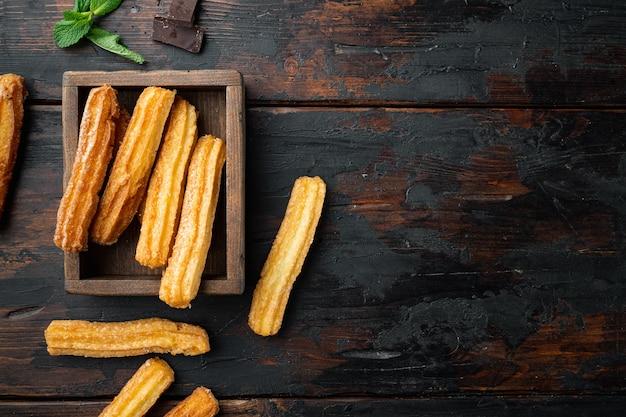 Churros con chocolate, cocina tradicional española, sobre fondo antiguo de mesa de madera oscura, vista superior plana con espacio para texto, copyspace