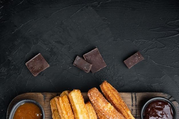 Churros con chocolate, cocina tradicional española, sobre negro