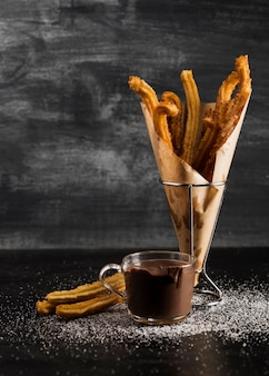 Churros ina vidrio y chocolate vista larga