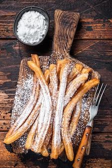 Churros de postre español con azúcar en polvo en una bandeja de madera. madera oscura