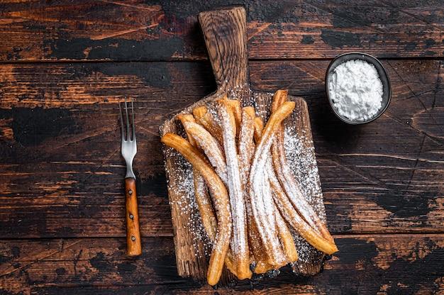 Churros de postre español con azúcar en polvo en una bandeja de madera