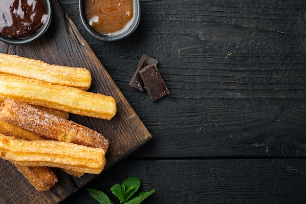 Churros de postre tradicional español con azúcar y chocolate, sobre fondo de mesa de madera negra, vista superior plana con espacio para texto, copyspace
