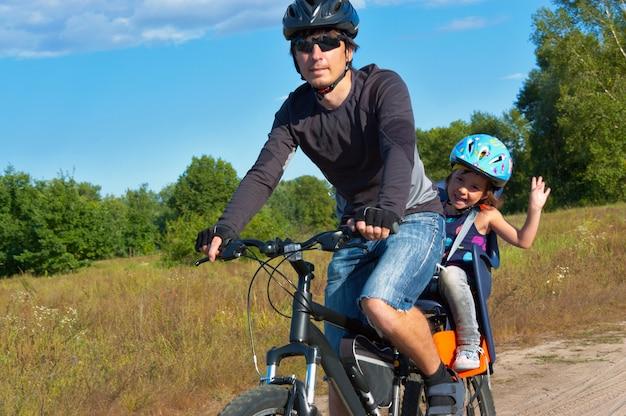 Ciclismo familiar. padre con niño feliz andar en bicicleta al aire libre