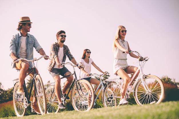 Ciclismo con mejores amigos. grupo de jóvenes en bicicleta y mirando feliz