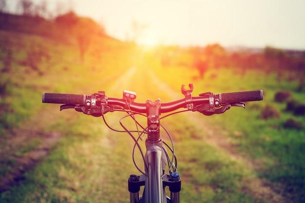 Ciclismo de montaña cuesta abajo descendiendo rápidamente en bicicleta. vista desde los ojos de los ciclistas.