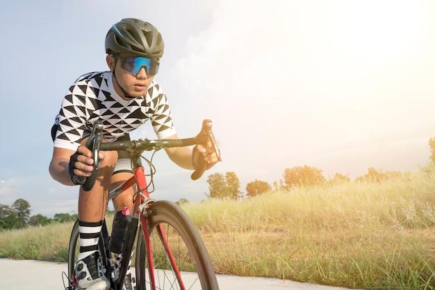 Ciclista adulto de asia montar bicicleta moderna en la mañana con hermoso amanecer.