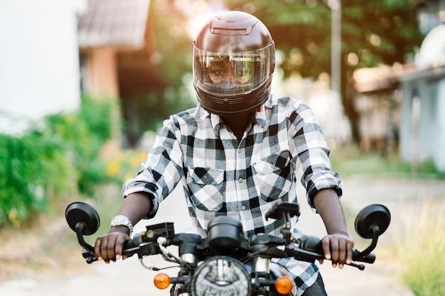 Ciclista africano en el casco y gafas conduciendo una motocicleta.