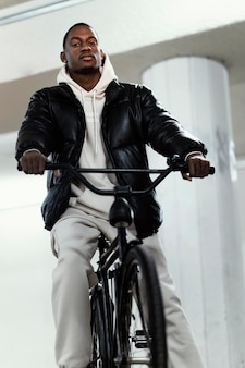 Ciclista afroamericano montando su bicicleta vista baja