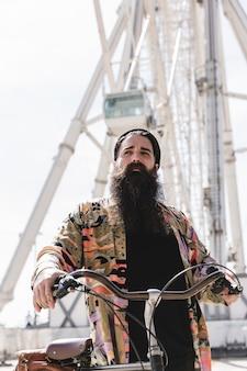 Ciclista barbudo de pie en el parque de atracciones junto a la noria
