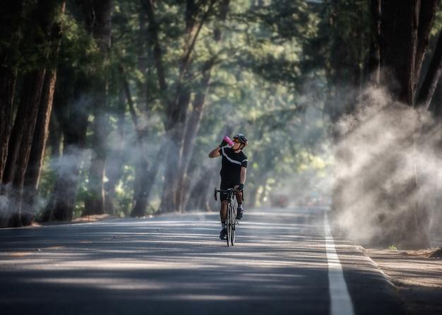 El ciclista bebe agua de la botella deportiva.