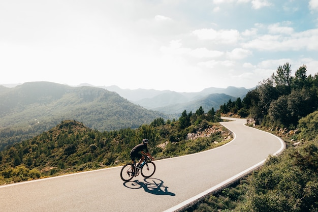 Ciclista en bicicleta al atardecer en una carretera de montaña