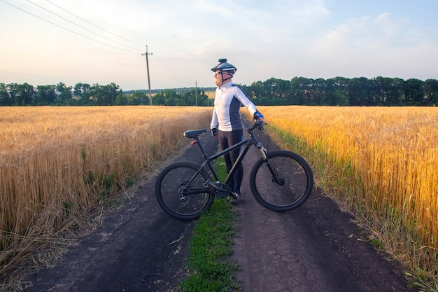 El ciclista con la bicicleta en un campo mirando la puesta de sol. deportes y pasatiempos. actividades al aire libre