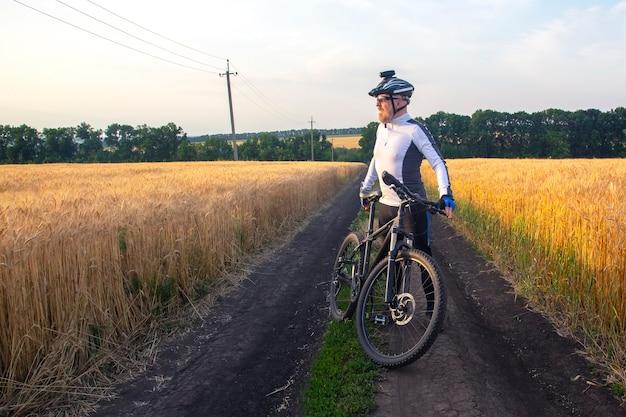 Ciclista con la bicicleta en un campo viendo la puesta de sol. deportes y pasatiempos. actividades al aire libre