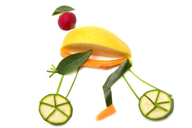 Ciclista con bicicleta hecha con frutas y verduras.