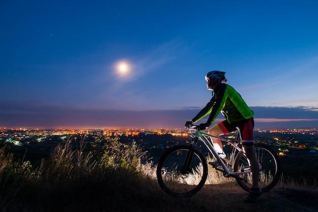Ciclista con bicicleta de montaña en la cima de la colina.