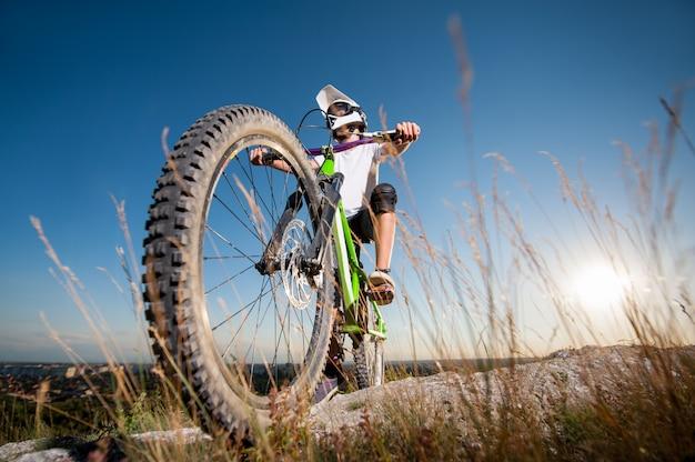 Ciclista con bicicleta de montaña en la colina bajo el cielo azul