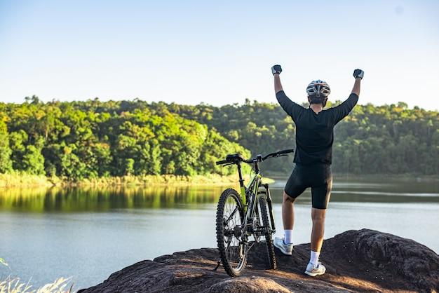 Ciclista de bicicleta de montaña de pie en la cima de una montaña con bicicleta
