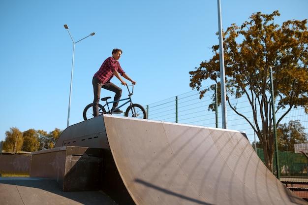 Ciclista de bmx haciendo truco, adolescente en entrenamiento en skatepark. deporte extremo en bicicleta, ejercicio de ciclo peligroso, riesgo de montar en la calle, andar en bicicleta en el parque de verano