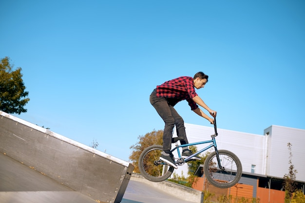 Ciclista de bmx haciendo truco en las escaleras, adolescente en entrenamiento en skatepark. deporte extremo en bicicleta, ejercicio de ciclo peligroso, riesgo de montar en la calle, andar en bicicleta en el parque de verano