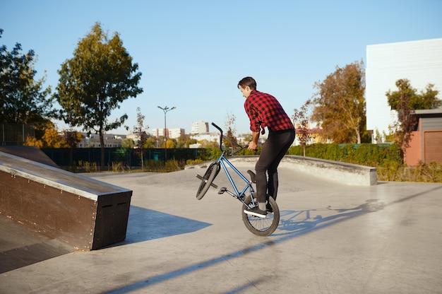 Ciclista de bmx masculino haciendo truco, entrenando en skatepark. deporte extremo en bicicleta, ejercicio de ciclo peligroso, riesgo de montar en la calle, andar en bicicleta en el parque de verano