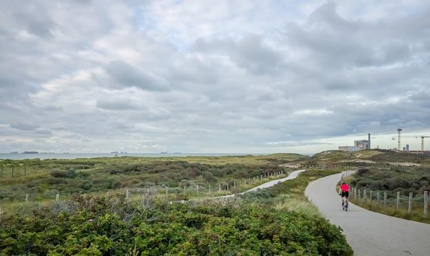 Ciclista de carreras en las dunas y playas del sur de la haya, scheveningen