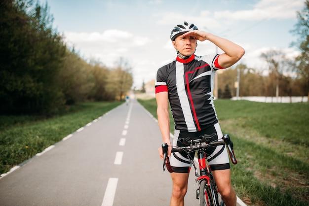 Ciclista en casco y ropa deportiva en bicicleta deportiva