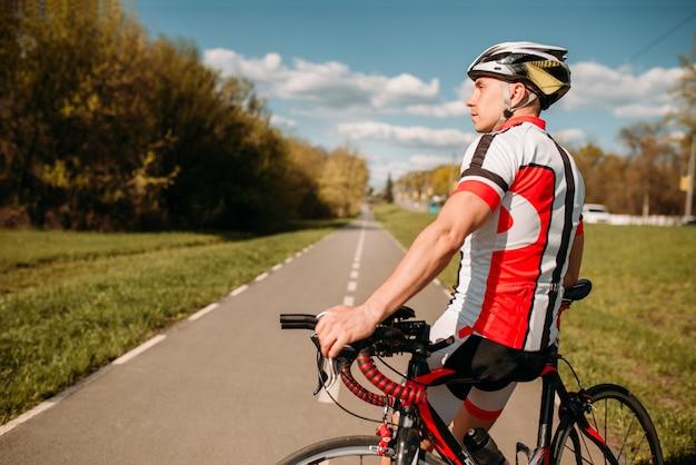 Ciclista en casco y ropa deportiva, entrenamiento de ciclismo en carretera asfaltada.