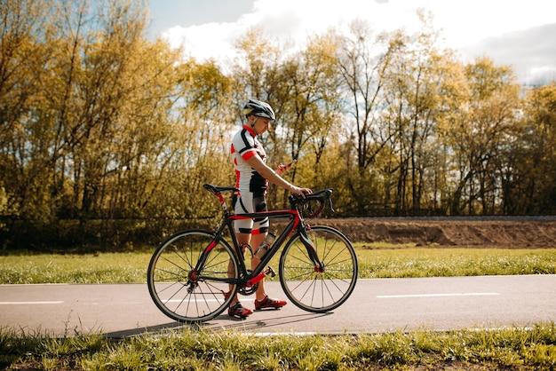 Ciclista en casco y ropa deportiva, entrenamiento de ciclocross en carretera asfaltada.