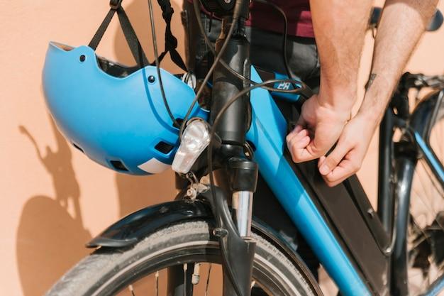 Ciclista de cerca asegurando la batería de la bicicleta eléctrica
